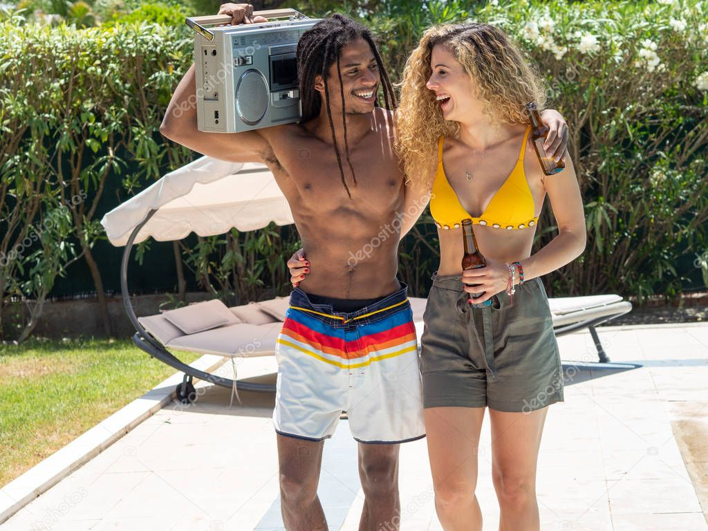 Interracial couple, black man and Caucasian woman walk with a cassette radio by the pool.