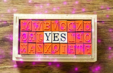 YES - isolated abstract in wood type stamps against wooden background with pink sparkle and copy space.