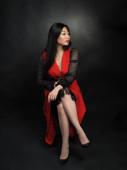 Asiatische Frau Modell in langem Kleid sitzt und posiert im Studio vor schwarzem Hintergrund