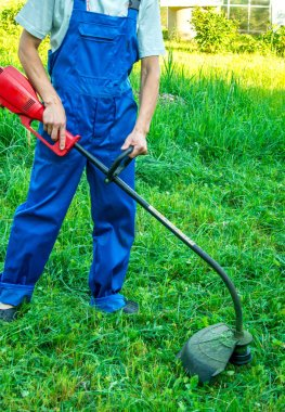 A man with a lawn mower on green grass.