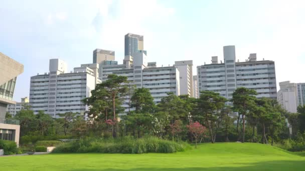 Seoul, Republic of Korea - August 2019: Green lawn with trees, new residential buildings in the background.