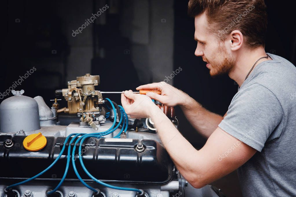 Close-up of an auto mechanic smiling repairs the engine of a lorry or bus, concept repair in a garage, car repair shop.