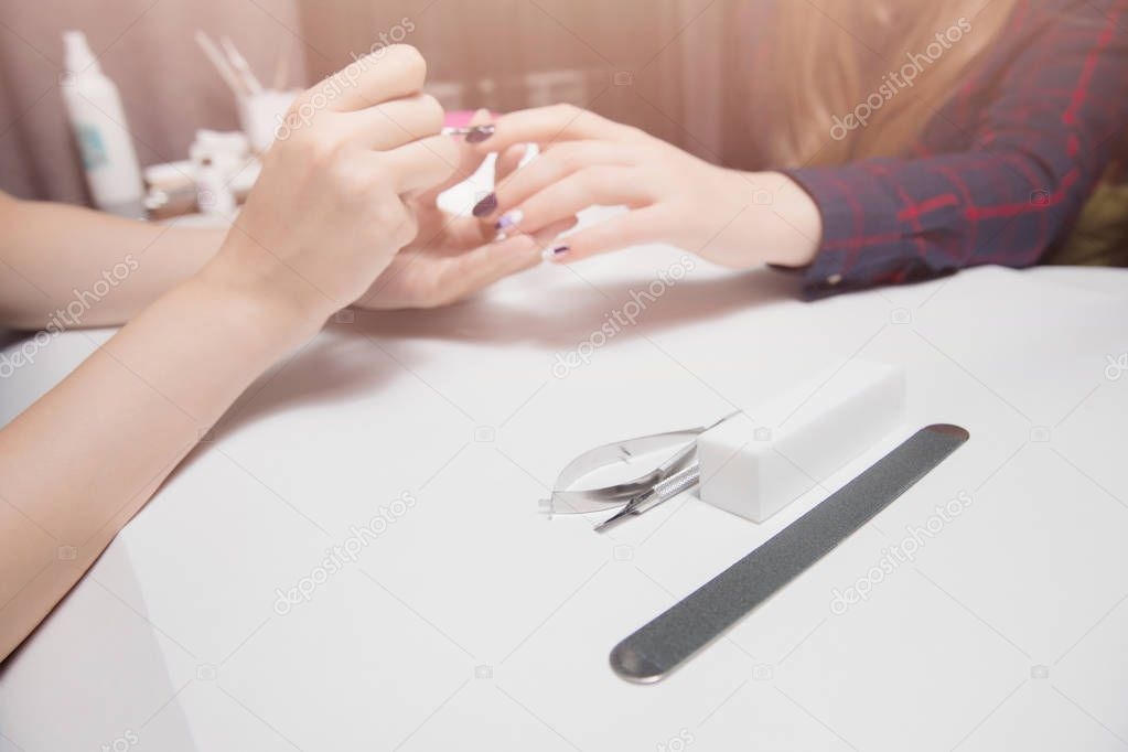 Manicure at beauty salon. Applying gel coating to girl with long hair. Close-up, warm lighting. Focus on tools, saws