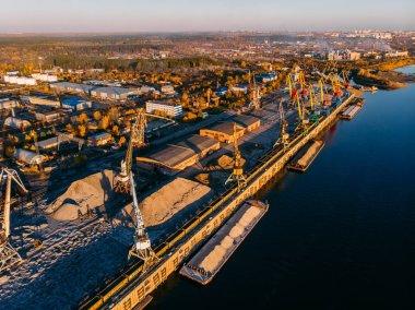 Port river cranes loading ships on barges delivery, sunset