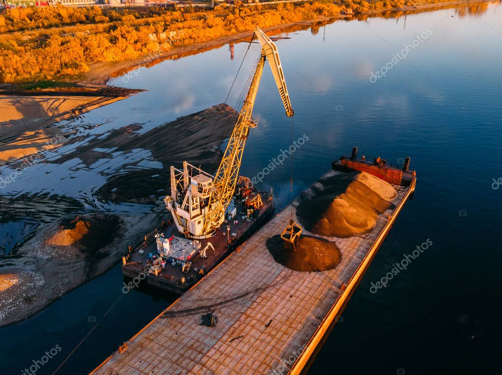 Crane is loading sand and gravel onto barge ship for river transport