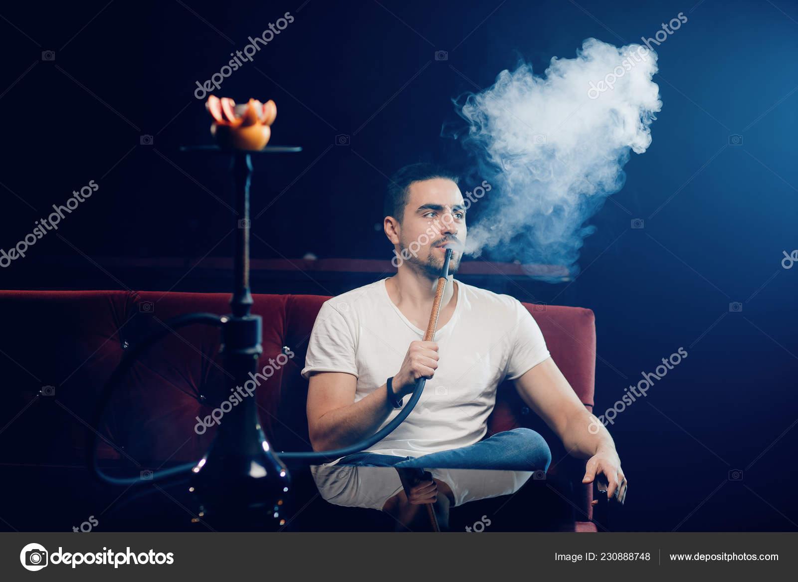 Young guy smoking hookah alone in shisha lounge bar closeup stock photo