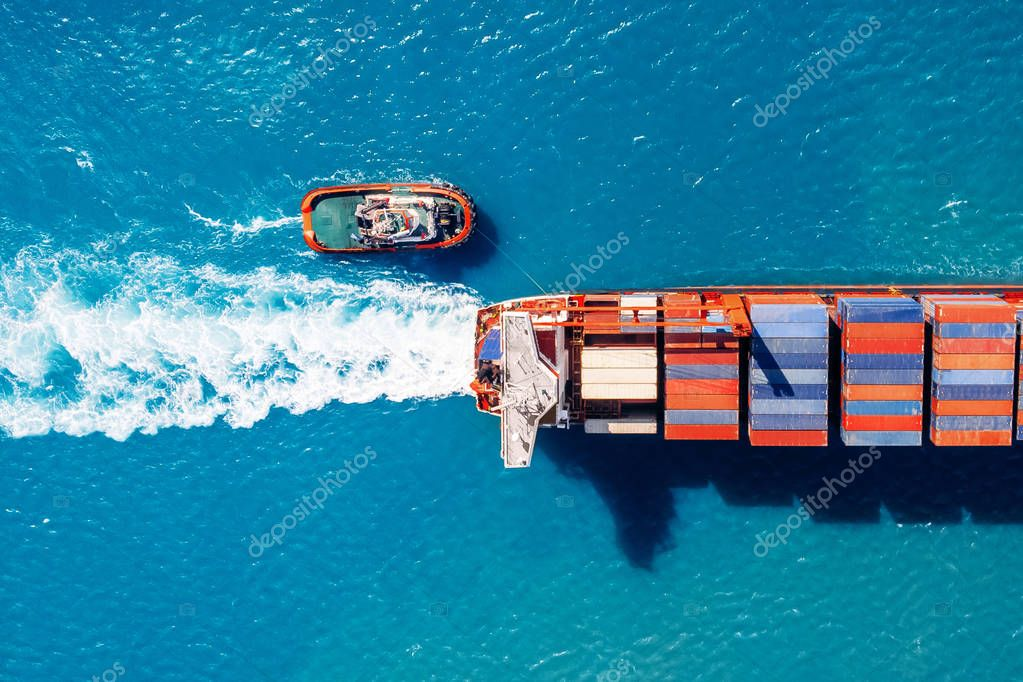 Tugboat parks in port Cargo ship with containers against blue sea, top view. Logistics delivery concept