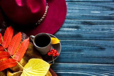 Hat burgundy or marsala color on a gray wooden background with autumn red, yellow leaves and cup of coffee or tea. Fashion trend autumn, winter, coziness, comfort concept