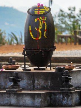 Shiva Lingam, Shiva Lingas with Om symbol painted on, wrapped around with the Tears of Shiva (Rudraksha) at meditation maze to practice walking meditation in Dhulikhel, Nepal stock vector