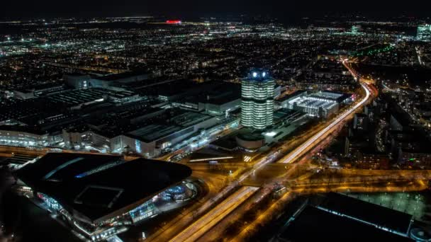 Německo, Mnichov - osvětlené ústředí BMW a BMW Welt s lehkými cestičkami z nočního provozu