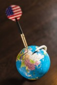 Fotografie USA concept targeting Russia. Darts arrow pricked on Russia on globe. American flag on arrow pointing Russia as target on the globe. The United States focused on Russia on the map.