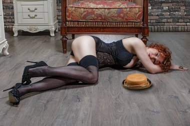 Beautiful, slender woman in a corset, on the floor with a straw hat