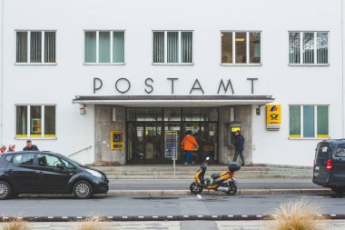 Bad Kissingen/Germany-31/12/18: people walk in and out of the Deutsche Post Office on Munchner Street. Deutsche Post AG is a German multinational package delivery and supply chain management company
