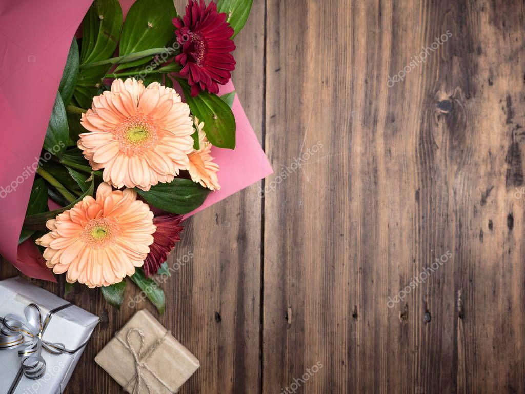 Bouquet of flowers on old wood background. Gift boxes tied with ribbon and rope with bows. Chrysanthemums with decorative plants for birthday card, invitation. Selective, blurred soft focus, top view.