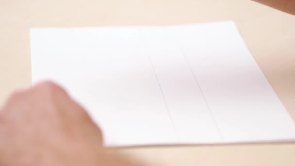 Calligraphist üres fehér írás. Szoros lövés. Oldalnézet. Kalligrafikus betűkkel. Mans kézi írás fehér papírra. Designer rajz ecsettel tollal. Szelektív lágy fókusz. Elmosódott háttér.