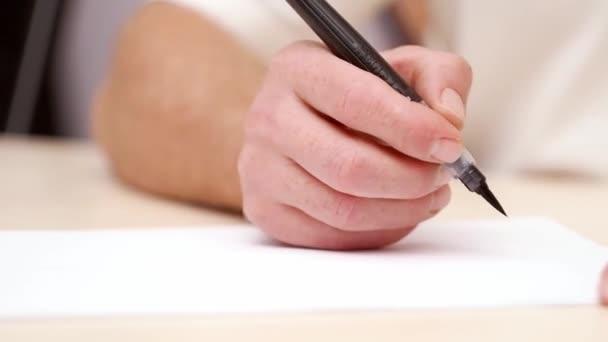 Mans leveleket tollal ecset kézzel. Szoros lövés. Elülső kilátás. Kalligrafikus betűkkel. Designer támaszkodva üres fehér ecset tollal. Művész dolgozik. Szelektív lágy fókusz. Elmosódott háttér.