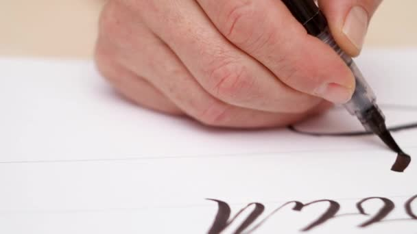 Calligraphist drawing on white blank. Close shot. Front view. Mans hand writing on white blank with brush pen. Calligraphic lettering. Designer drawing. Selective soft focus. Blurred background.