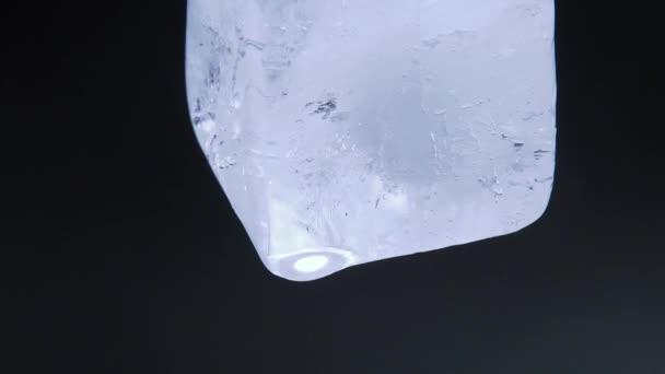 Makró videó lövés olvadó jég kocka fekete háttér. Jégkocka zuhan vízcseppek. Lövés közelről.