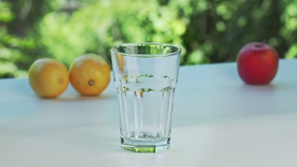 Ice cubes throwing in empty glass, close shot. Tree branches with green leaves swinging in wind on background. Yellow lemons and red apple on white desk. Selective soft focus. Blurred background