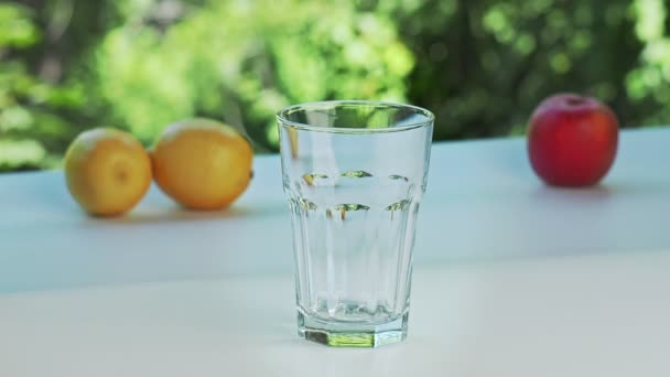 Handful of ice cubes throwing in empty glass, close shot. Yellow lemons, red apple and glass on white surface. Green trees on background. Selective soft focus. Blurred background.