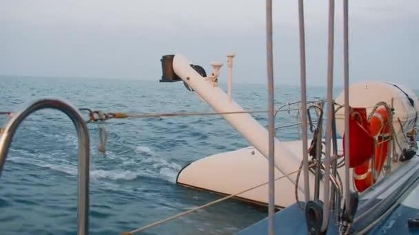 Katamaran pluje po moři při západu slunce. Pohled ze zádi člunu. Záchranný člun a vor, lanoví, vlny za jachtou proti obloze slunce. Prostřední plán