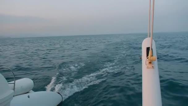 Yacht nyugodtan vitorlázás a tengeren naplementekor. Kilátás a hajó farán. Tengerre naplementekor. Hullámok a hajó mögött.