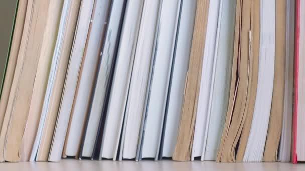 Dolly sklouzla po polici s knihami. Pohybuje se zleva doprava. Knihy jsou na poličce s knihami.