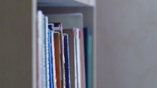 Dolly klouzala po hromádkách knih a pohybovala se zleva doprava podél regálu knih. Knihy různých výšek stojí bok po boku zblízka. Pohled na různé páteře knih.