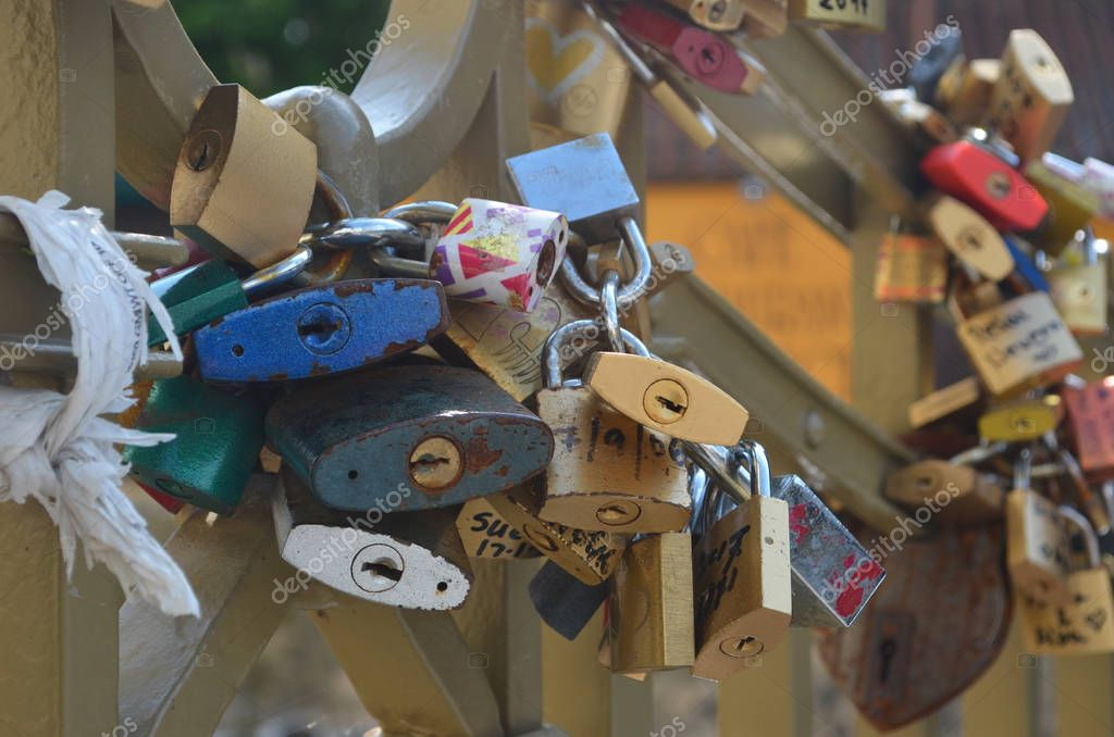 Paddlocks have been locked onto a 'love-lock bridge. The padlocks are of many colours, with dates and names written on them.