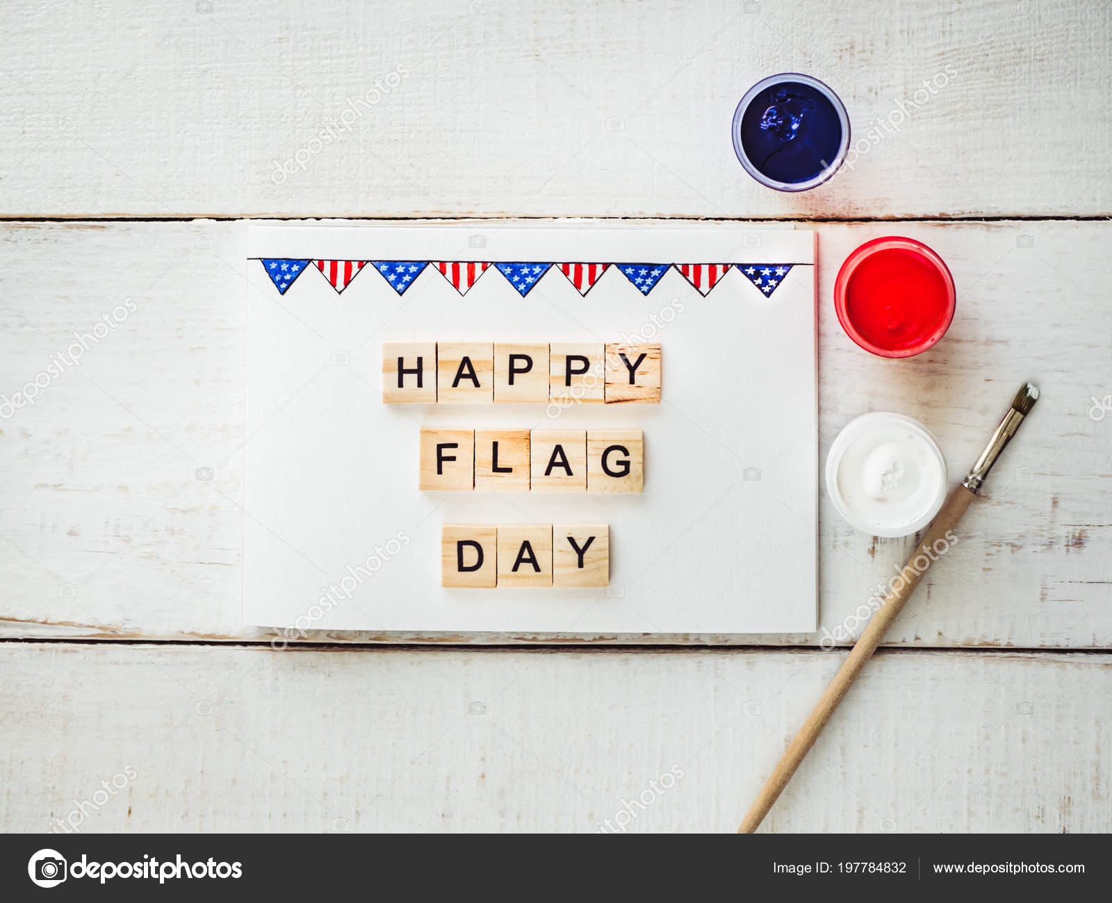 card with a pattern of the us flag and words of congratulations on the us flag day on a white vintage wooden table top view close up