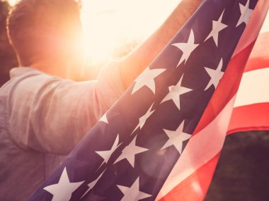 Attractive man holding waving in the wind US flag