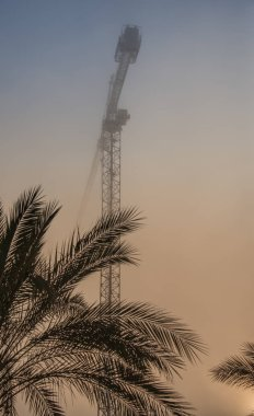 Construction crane against the background of a misty sky. Summer of Israel.