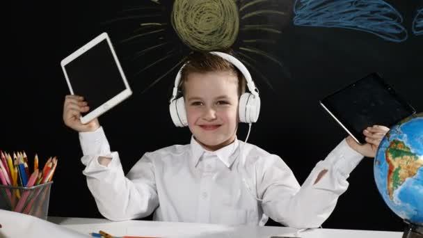 Koncepce školy. Roztomilý chlapec sedí za stolem s zeměkoule. a tabulí za ním. pozitivní školák v úsměvy sluchátka s tablety v ruce