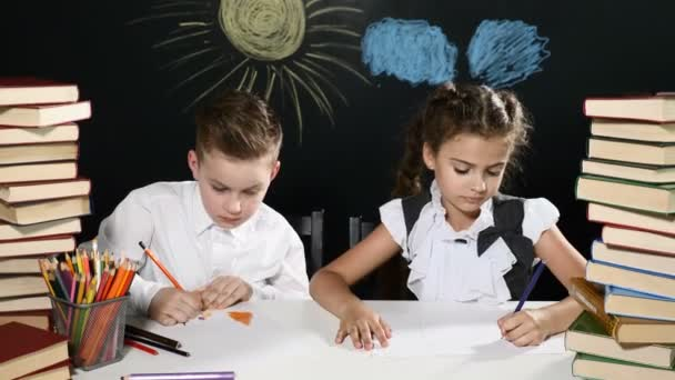 Modern iskola fogalmát. Fiú és lány ül az asztalon halomba rak-ból könyv. és egy táblára, mögöttük. Gyerekek vannak osztály tábla háttér. A diákok elfoglalt, rajz- és
