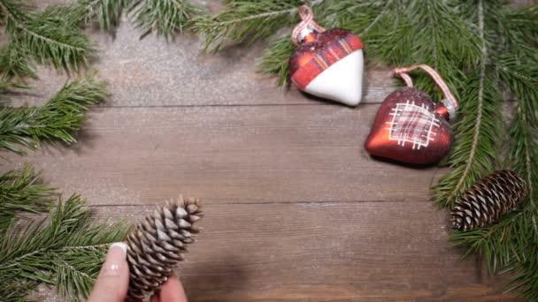 Silvestrovské a vánoční pohlednice. Jedle a vánoční dekorace umístěny na dřevěných pozadí. Pohled shora. Ženská ruka klade kužel tak, aby poskytnout prostor pro poznámky ve středu