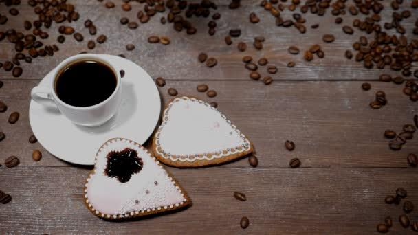 Jídlo umění. Dobré ráno koncept. šálek kávy a 2 gingersnaps ve tvaru srdce jsou na dřevěné pozadí. Kávová zrna padají v pomalém pohybu