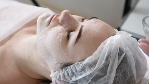 Junge hübsche Frau bekommen Verfahren im Beauty-Salon. Junge schöne dunkelhaarige Frau auf Couch. Kosmetikerin Gesichts Reinigungsschaum auf Gesicht auftragen