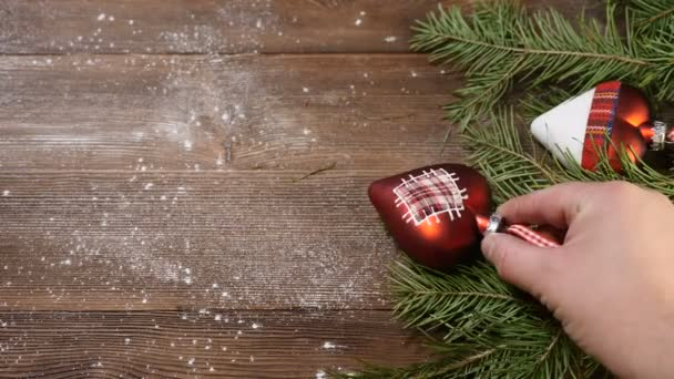 New Year and Merry Christmas 2019 2020. christmas tree with decorations on  wooden background. male hand adds another decoration ball