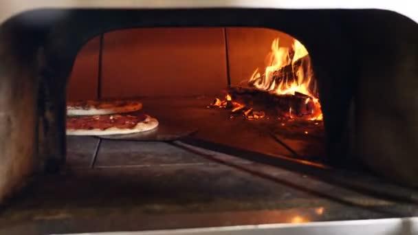 Pizza viene cotta nel pane pizza ristorante forno a legna tradizionale.  Cottura della pizza in cucina aperta ristorante fornetto per pizza chef.