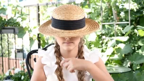 Portré fiatal vonzó mosolygó lány játszik egy szalmakalapot. Életmód fogalom. Boldog gyermekkor.