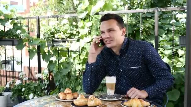 Pohledný mladý usmívající se muž sedí v kavárně mluvit na telefonu pít cappuccino