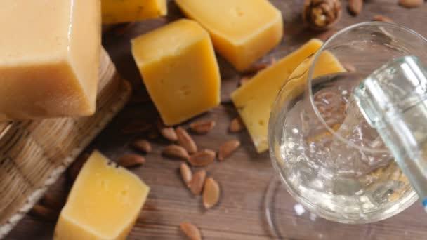 Víno a sýr. Jídlo umění. Různé druhy tvrdý sýr krásně surved na dřevěné pozadí. Bílé víno se nalije do sklenice na víno.