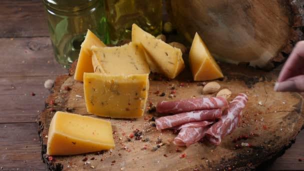 Rozmanitost sýrů na dřevěné pozadí. Ženská ruka přidá kousek prosciutto. Jídlo umění. Prezentace jídel