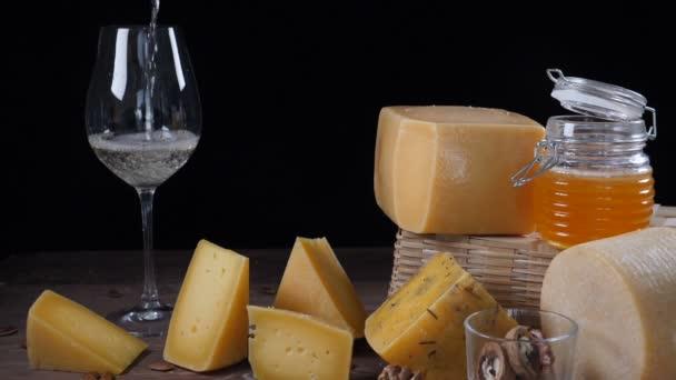 Sýr a víno. Množství sýra umístěného na dřevěné pozadí. víno se nalije do sklenice na víno v pomalém pohybu