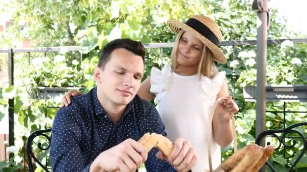 V pekárně. Mladý pohledný muž roztrhání francouzský chléb. Muž trhání bagetu na polovinu. Roztomilá holčička v sledování slaměný klobouk. 4k