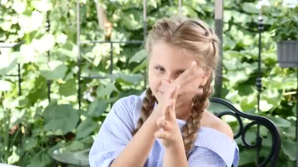 Cute young girl playing and having fun closing her eyes with fingers. Happy childhood. 4k