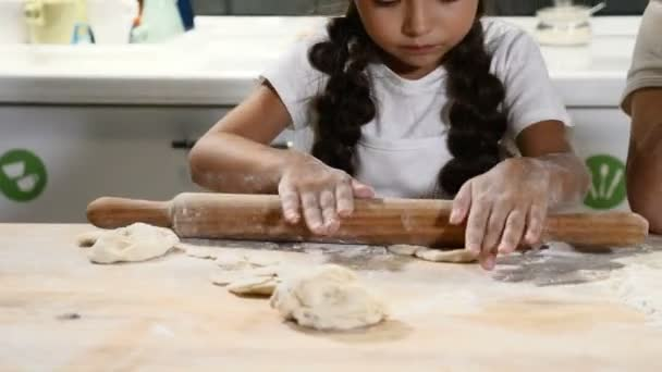 Kid bakery. Cute girl in chef hat rolling dough on kitchen table. Kid chef prepare cake. 4k