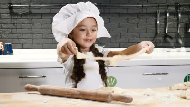 8db80f96dcc Portrait of little pretty girl in chef hat playing with dough