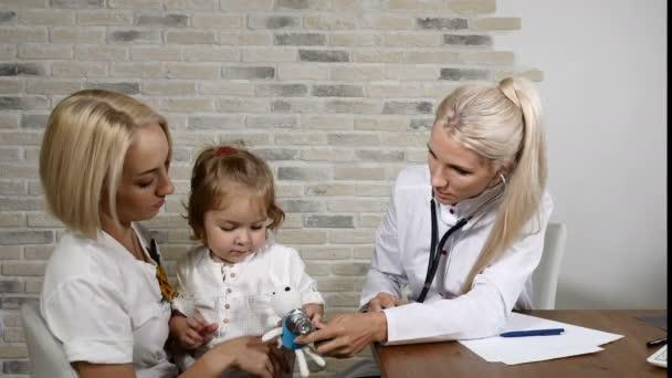 Untersuchung der Kindergesundheit. Die junge Mutter und ihre kleine hübsche Tochter besuchen den Hausarzt. freundlicher Kinderarzt. Arzt mit Phonendoskop und Spielzeug. 4k