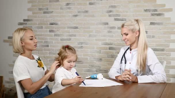 Untersuchung der Kindergesundheit. Die junge Mutter und ihre kleine hübsche Tochter besuchen den Hausarzt. freundlicher Kinderarzt. 4k